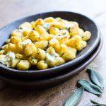 Ñoquis dorados de polenta y ricotta, con mantequilla y salvia.